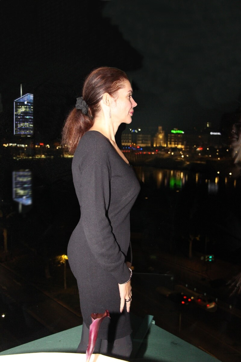 Europe, Lyon, les Trois Dômes, Christian Lherm, Amélie en robe rodier noire moulante, cambrée, devant l'une des baies vitrées de la salle. Quais du Rhône.