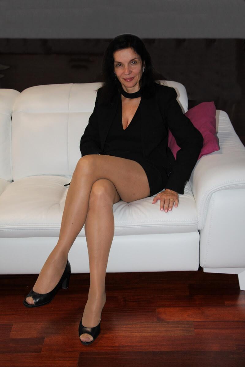 Amélie, en veste noire, décolleté, mini-jupe, collants chair. Jolies jambes. Revealing neckline, beautiful legs.